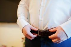 Jeune ceinture de port d'homme fort son jour du mariage Marié de matin photographie stock libre de droits