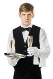 Jeune champagne de portion de serveur sur un plateau images stock