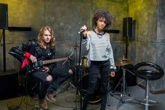 Jeune chanteur se tenant avec le microphone tandis qu'homme jouant la guitare électrique Photographie stock libre de droits