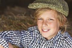 Jeune chapeau plat blond heureux de chemise de plaid d'enfant de garçon image stock