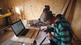 Jeune charpentier audacieux avec le dessin de moustache dans son atelier clips vidéos