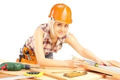 Jeune charpentier féminin travaillant et regardant l'appareil-photo photos libres de droits