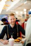 Jeune cheeseburger mangeur d'hommes dans le wagon-restaurant Photos libres de droits