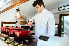 Jeune chef beau préparant des boulettes de viande dans un camion de nourriture image libre de droits