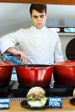 Jeune chef beau préparant des boulettes de viande dans un camion de nourriture images libres de droits