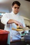 Jeune chef beau préparant des boulettes de viande dans un camion de nourriture photographie stock