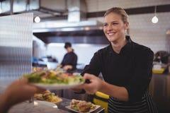 Jeune chef féminin attirant donnant la salade grecque fraîche au serveur Images libres de droits