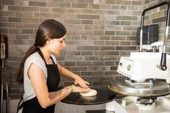 Jeune chef plaçant la pâte sur la machine de presse pour faire la pizza photo stock