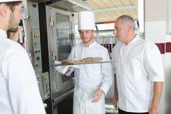 Jeune chef pour mettre la nourriture en four image stock