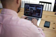 Jeune chef sûr du département se reposant dans le bureau de l'ordinateur portable Photo stock