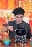 Jeune cheff beau préparant un dîner suisse gastronome de fondue avec des fromages assortis et un pot passionné de fondue de froma Image stock