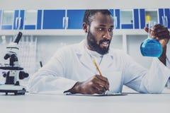 Jeune chimiste assidu faisant quelques notes image stock