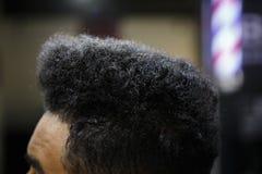 Jeune client d'homme de couleur obtenir la nouvelle coupe de cheveux dans le raseur-coiffeur photos stock