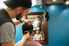 Jeune client de coupe de styliste à l'espace libre de miroir Photographie stock libre de droits