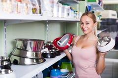Jeune client féminin choisissant des cuvettes pour des animaux familiers Photo stock