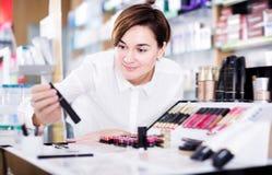 Jeune client féminin recherchant des articles de maquillage photographie stock