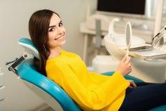 Jeune client heureux de femme regardant le miroir avec le sourire toothy le bureau dentaire image libre de droits
