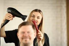 Jeune coiffeur Drying Male Hair par le dessiccateur de coup image libre de droits