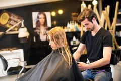Jeune coiffeur masculin avec le client Photographie stock