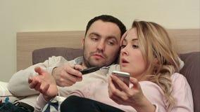 Jeune combat de couples, discutant dans le lit la nuit parce que service de mini-messages de femme quelqu'un utilisant le smartph banque de vidéos
