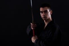 Jeune combattant d'arts martiaux avec le katana photo stock