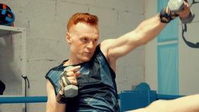 Jeune combattant de formation professionnelle faisant des exercices dynamiques avec des haltères clips vidéos
