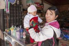 Jeune commerçante chinoise de fille tenant un bébé sur les mains Photo libre de droits