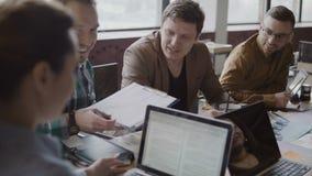 Jeune compagnie de démarrage au bureau à la mode Le groupe de personnes multi-ethnique discutant des données financières emploien Image stock
