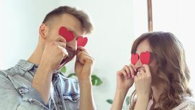 Jeune concept de jour du ` s de valentine de saint de couples à la maison ensemble près de la fenêtre jouant avec les coeurs de p banque de vidéos