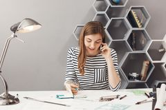 Jeune concepteur beau d'entrepreneur avec les cheveux foncés dans la chemise rayée parlant au téléphone avec la discussion de cli photographie stock