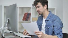 Jeune concepteur créatif Reading Documents et fonctionnement sur le bureau banque de vidéos