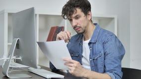 Jeune concepteur créatif Reading Documents, passant par le contrat banque de vidéos