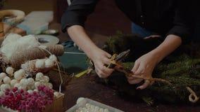 Jeune concepteur de sourire mignon de femme préparant la guirlande à feuilles persistantes d'arbre de Noël Fabricant de décor de  banque de vidéos