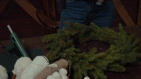 Jeune concepteur de sourire mignon de femme préparant la guirlande à feuilles persistantes d'arbre de Noël Fabricant de décor de  clips vidéos