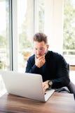 Jeune concepteur heureux travaillant sur l'ordinateur portable du café photo stock