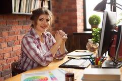 Jeune concepteur ou photographe éditeur de sourire de femme dans le bureau travaillant à l'ordinateur et au comprimé graphique illustration stock