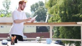Jeune concepteur Reading Documents, se tenant dans le balcon extérieur clips vidéos