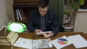 Jeune concepteur tenant le PC de comprimé et vérifiant des papiers d'affaires sur sa table clips vidéos