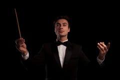 Jeune conducteur élégant dirigeant sa bande d'orchestre Images stock