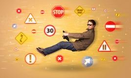Jeune conducteur avec des panneaux routiers autour de lui Image stock