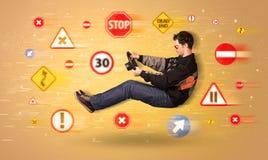 Jeune conducteur avec des panneaux routiers autour de lui Photographie stock