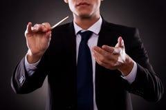 Jeune conducteur d'orchestre dirigeant avec son bâton Photographie stock libre de droits