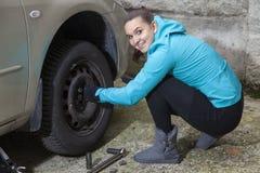 Jeune conducteur de sourire de femme remplaçant des pneus Photo stock