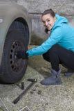 Jeune conducteur de sourire de femme remplaçant des pneus Photo libre de droits