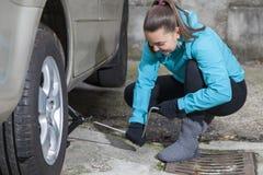 Jeune conducteur de sourire de femme remplaçant des pneus Image stock