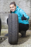 Jeune conducteur de sourire de femme remplaçant des pneus, montrant le signe CORRECT Images stock