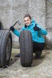 Jeune conducteur de sourire de femme remplaçant des pneus, montrant le signe CORRECT Photo libre de droits