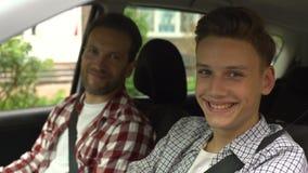 Jeune conducteur et son père souriant dans la caméra, années de l'adolescence obtenant le permis de conduire banque de vidéos