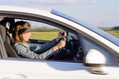 Jeune conducteur féminin Driving une voiture sur la route photo stock