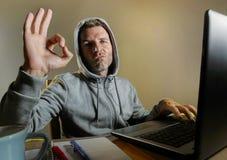Jeune connaisseur de regard attirant et dangereux d'ordinateur de pirate informatique travaillant sur l'ordinateur portable entai image libre de droits
